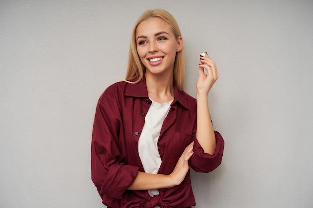 Portret van positieve jonge blonde vrouw met casual kapsel nemen oortje en opzij kijken met charmante brede glimlach, geïsoleerd op lichtgrijze achtergrond