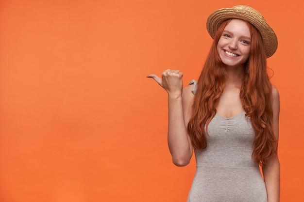 Portret van positieve jonge foxy langharige vrouw op zoek naar camera met charmante glimlach, staande over oranje achtergrond met opgeheven duim opzij tonen, vrijetijdskleding dragen