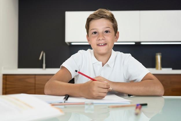 Portret van positieve jonge jongen die huiswerk doet