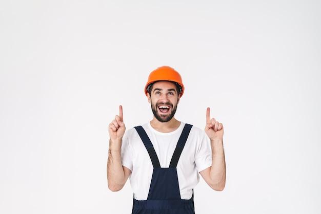 Portret van positieve jonge man bouwer in helm poseren geïsoleerd over witte muur opzij wijzend.