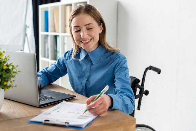Portret van positieve jonge vrouw die op het kantoor werkt