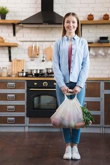 Portret van positieve jonge vrouw die organische groenten houdt