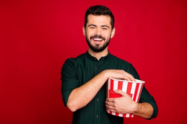 Portret van positieve kerel hebben pauze pauze kijken naar grappige film houden grote rode gestreepte pop corn box genieten van recreatie dragen casual stijl kleding
