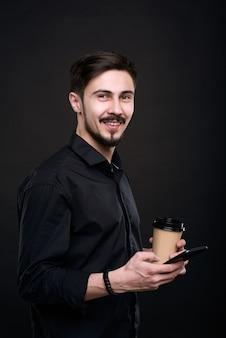 Portret van positieve knappe manager koffie drinken uit wegwerp beker en draagbaar apparaat gebruiken