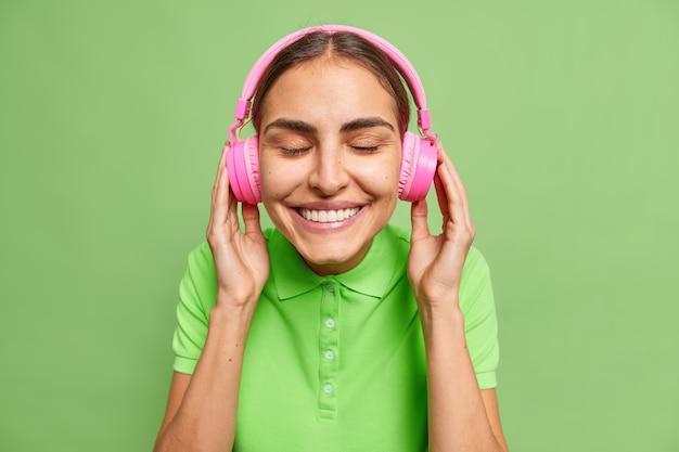 Portret van positieve knappe vrouw met zachte glimlach zet draadloze koptelefoon op gekleed in casual t-shirt geïsoleerd over groene muur luistert favoriete afspeellijst
