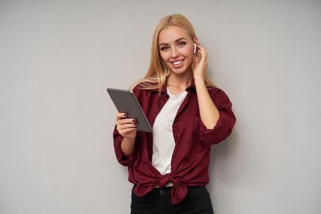 Portret van positieve langharige blonde jongedame oortelefoons dragen en hand op haar oor houden, vrolijk op zoek naar camera met charmante glimlach, die zich voordeed op de lichtgrijze achtergrond