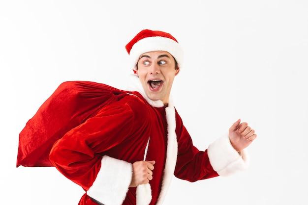 Portret van positieve man 30s in kerstman kostuum en rode hoed met cadeau tas over schouder