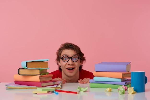 Portret van positieve man met bril draagt in rood t-shirt, verstopt aan de tafel met boeken, kijkt naar de camera en lacht, ziet er vrolijk uit, geïsoleerd op roze achtergrond.