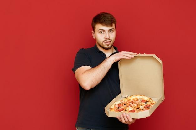 Portret van positieve man staat en opent doos met heerlijke verse pizza