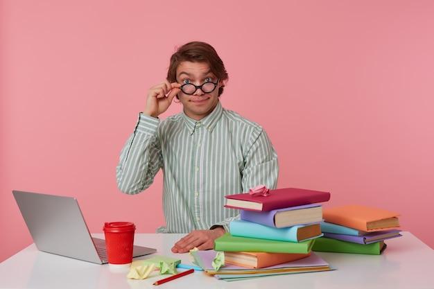 Portret van positieve man student in glazen draagt in rood t-shirt, zit bij de tafel en werkt met notitieboekje en boeken, voorbereid voor examen, kijkt door glazen, geïsoleerd op roze achtergrond.
