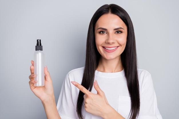 Portret van positieve meisje promotor adverteren nieuwe hygiëne coronavirus antibacteriële dispenser punt wijsvinger dragen witte t-shirt geïsoleerd over grijze kleur achtergrond