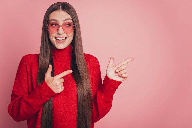 Portret van positieve meisje promotor punt wijsvinger copyspace geïsoleerde roze kleur achtergrond