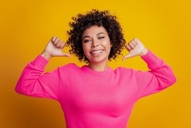 Portret van positieve meisjes directe vingers duimen zichzelf gele kleur achtergrond