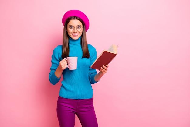 Portret van positieve meisjesachtig meisje hipster student in het buitenland houden papieren boek warme cappuccino koffiekopje genieten na studieweekends draag een goede paarse outfit.