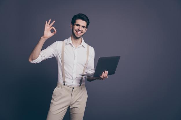 Portret van positieve rijke rijke bedrijfseigenaar man handelaar werk computer ok teken dragen goed uitziende outfit.