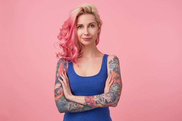 Portret van positieve schattige dame met roze haar en getatoeëerde handen, permanent en glimlachend, gekleed in een blauw shirt. mensen en emotie concept.