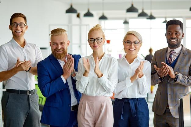 Portret van positieve sex tussen verschillendre rassen team camera kijken in het kantoor