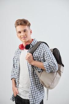 Portret van positieve student die met rugzak voorzijde bekijkt, geïsoleerd op lichtgrijs