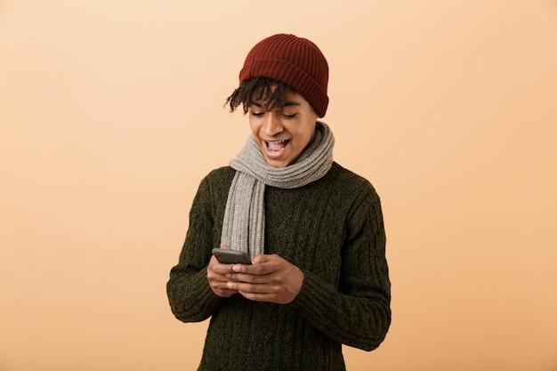 Portret van positieve tiener man met hoed en sjaal met behulp van mobiele telefoon, geïsoleerd over gele muur