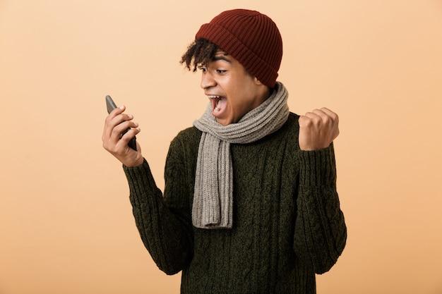Portret van positieve tiener man met hoed en sjaal schreeuwen en smartphone gebruiken, geïsoleerd over gele muur