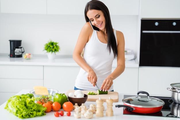 Portret van positieve vrolijk meisje ontspannen weekends koken binnenlands diner avondmaal maaltijd spreken op mobiel met haar vriend gesneden ingrediënt groene komkommer op snijplank in witte keuken huis