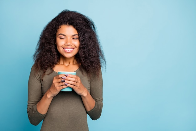 Portret van positieve vrolijke afro-amerikaanse meid houdt beker mok met hete koffie geniet van geur kalm voelen vredig in het weekend vrije tijd dragen casual stijl trui geïsoleerd over blauwe kleur muur