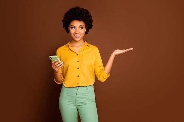 Portret van positieve vrolijke afro-amerikaanse meisje gebruik smartphone houden hand display online sociaal netwerk korting aanbevelen promotie-advertenties dragen gele outfit geïsoleerde bruine kleur