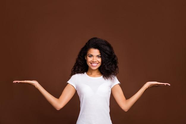 Portret van positieve vrolijke afro-amerikaanse meisje promotor houden hand demonstreren meting vergelijking advertenties promotie selecteren suggereren stijlvolle outfit dragen.
