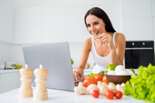 Portret van positieve vrolijke huisvrouw gebruik haar laptop koken informatie kijken culinaire films wilt bereiden biologische maaltijd dragen witte singlet in keuken huis binnenshuis bereiden