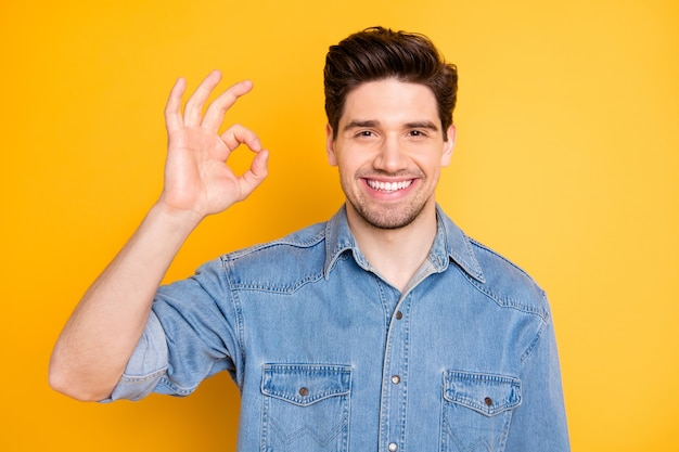 Portret van positieve vrolijke kerel promotor toon goed teken adviseren promo-advertenties dragen casual stijl kleding geïsoleerd over gele kleur muur