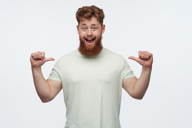 Portret van positieve vrolijke man met grote baard en rood haar draagt blanco t-shirt, wijzend met duimen zelf