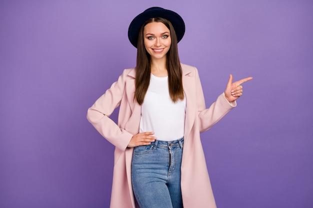 Portret van positieve vrolijke meid in pastel jas punt wijsvinger copyspace raden aan om geselecteerde advertentie promotie te dragen, goed uitziende kleding te dragen geïsoleerd over paarse kleur achtergrond