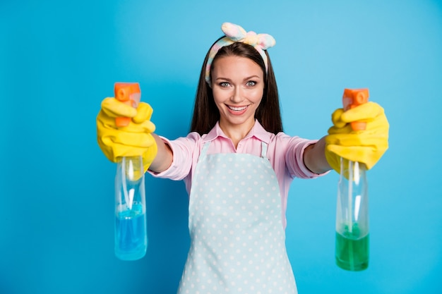 Portret van positieve vrolijke meid, schoonmaakster, houd spuitfles vast