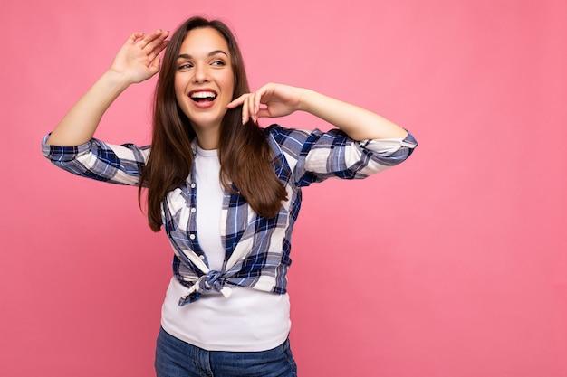 Portret van positieve vrolijke modieuze vrouw in hipster outfit geïsoleerd op roze achtergrond met kopie ruimte.