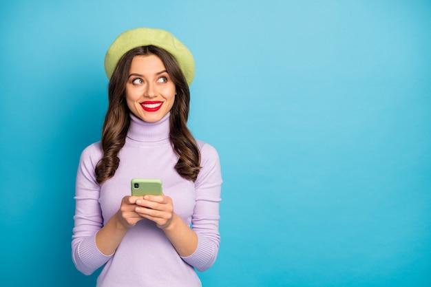 Portret van positieve vrolijke rode lisp vrouw chill gebruik smartphone repost sociale media nieuws look copyspace gok slijtage stijl stijlvol trendy trui hoofddeksels geïsoleerd over blauwe kleur muur