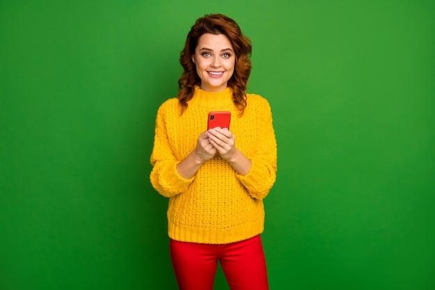 Portret van positieve vrolijke verslaafde vrouw gebruik smartphone geniet van chatten met sociale media vrienden dragen stijl trendy pullover geïsoleerd over heldere glans kleur muur