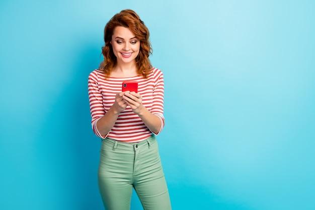 Portret van positieve vrolijke vrouw gebruik smartphone lees sociale media nieuwsinformatie draag stijlvolle trui geïsoleerd over blauwe kleur