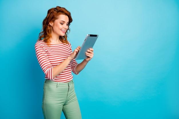 Portret van positieve vrolijke vrouw gebruik tablet rust ontspannen chillen zoeken blogpost apps dragen goed uitziende trui geïsoleerd over blauwe kleur