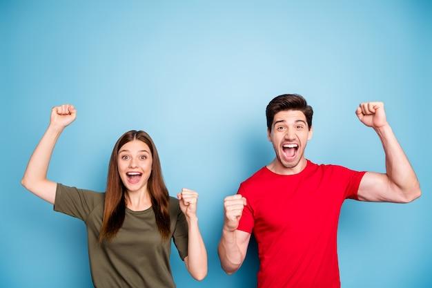 Portret van positieve vrolijke vrouw man echtgenoten vieren loterij overwinning vuisten heffen schreeuwen wow ja voel opgetogen draag moderne jeugduitrusting geïsoleerd op blauwe kleur achtergrond