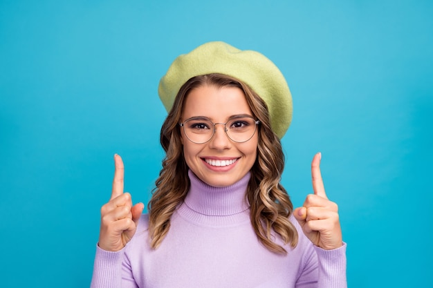 Portret van positieve vrolijke wijsvinger copyspace van het meisjespunt op blauwgroen muur