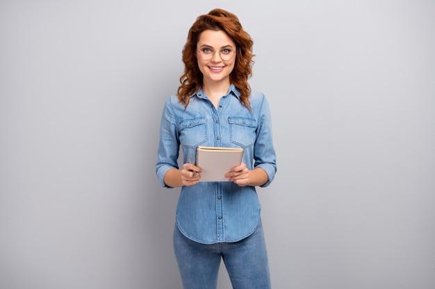 Portret van positieve vrolijke zelfverzekerde koele vrouw jonge professor greep voorbeeldenboek lezen lezing klas draag goed kijken moderne kleding geïsoleerd over grijze kleur muur