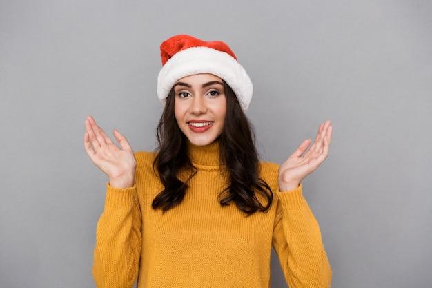 Portret van positieve vrouw die de rode hoed van de kerstman draagt die en pret glimlacht heeft, geïsoleerd over grijze achtergrond