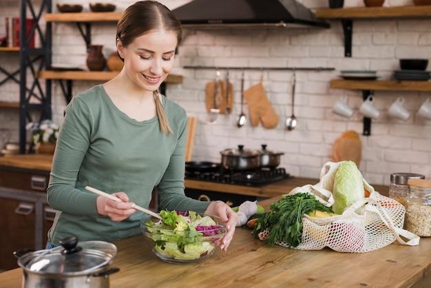 Portret van positieve vrouw die een verse salade voorbereidt