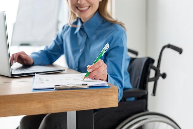 Portret van positieve vrouw die op het kantoor werkt