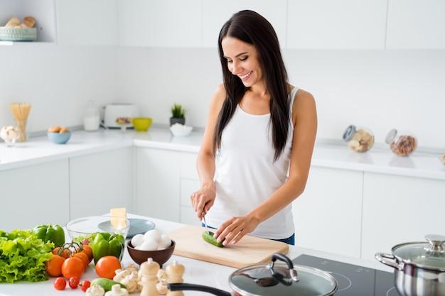 Portret van positieve vrouw huisvrouw bereiden ochtendmaaltijd gebruik keukengerei gesneden komkommer op houten snijplank binnenshuis binnenshuis