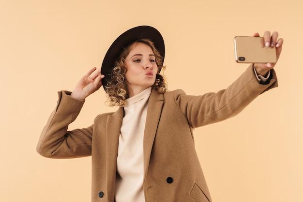 Portret van positieve vrouw in hoed geïsoleerd op beige muur nemen selfie door mobiele telefoon kussen te blazen.
