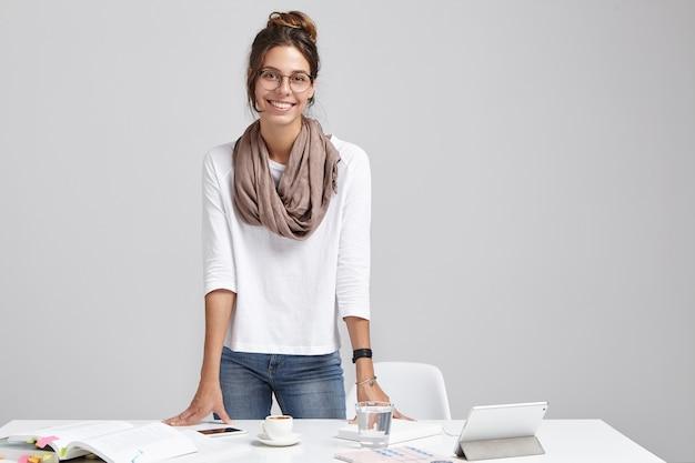 Portret van positieve vrouwelijke student bereidt zich voor op lessen, leest wetenschappelijke literatuur