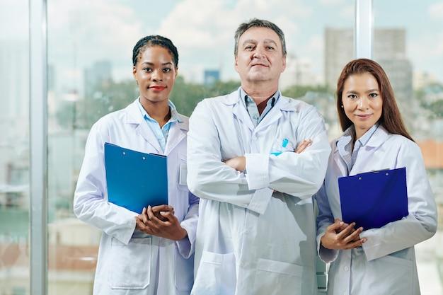 Portret van positieve zelfverzekerde artsen in witte labjassen die zich in kliniek bevinden en aan voorzijde glimlachen