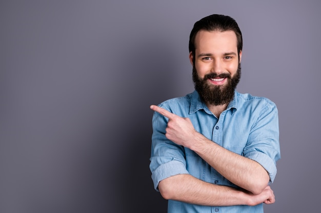 Portret van positieve zelfverzekerde coole kerel promotor punt wijsvinger copyspace huidige advertenties promotie pick tips dragen goed uitziende kleding geïsoleerd over grijze kleur muur