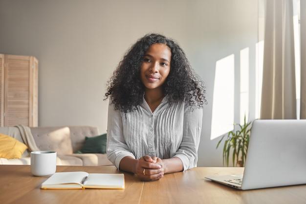 Portret van positieve zelfverzekerde jonge donkere vrouwelijke leraar met omvangrijke kapsel klaar voor online les, zittend aan een bureau met laptop, koffie en beurt in kantoor aan huis interieur